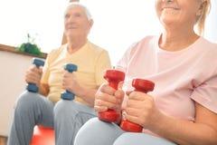 Los pares mayores ejercitan juntos en casa haciendo aeróbicos con el primer de los dubbells Foto de archivo