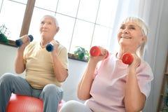 Los pares mayores ejercitan juntos en casa haciendo los aeróbicos que llevan a cabo dubbells Fotografía de archivo