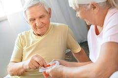 Los pares mayores ejercitan juntos en casa la atención sanitaria que da la comida sana Fotos de archivo