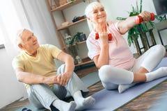 Los pares mayores ejercitan juntos en casa la atención sanitaria que se sienta celebrando la sonrisa de las pesas de gimnasia Fotografía de archivo libre de regalías