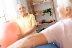 Los pares mayores ejercitan juntos en casa la atención sanitaria que sostiene las bolas que miran en uno a detrás ven Foto de archivo