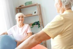 Los pares mayores ejercitan juntos en casa la atención sanitaria que sostiene las bolas que miran en uno a detrás ven Imagenes de archivo