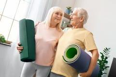 Los pares mayores ejercitan juntos en casa la atención sanitaria que sostiene las esteras de la yoga que miran en uno a Imagen de archivo libre de regalías