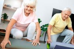 Los pares mayores ejercitan juntos en casa la estera de la yoga del balanceo de la atención sanitaria Imagenes de archivo