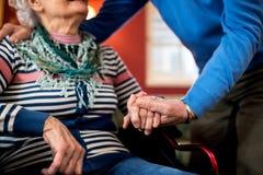 Los pares mayores en amor, hombre mayor toman cuidado de su esposa en rueda foto de archivo
