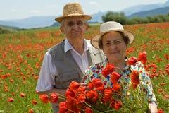 Los pares mayores en la amapola colocan disfrutar de verano foto de archivo libre de regalías