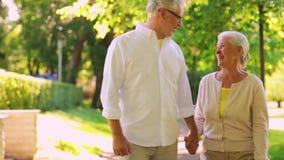 Los pares mayores felices que caminan en la ciudad del verano parquean almacen de metraje de vídeo