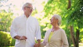 Los pares mayores felices que caminan en la ciudad del verano parquean almacen de video