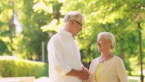 Los pares mayores felices que hablan en la ciudad del verano parquean almacen de video