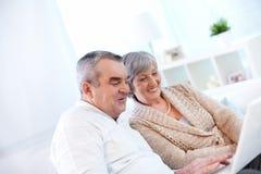 Los pares mayores felices utilizan el ordenador fotos de archivo libres de regalías