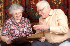 Los pares mayores leen las noticias y sonríen foto de archivo libre de regalías