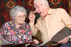 Los pares mayores leen las noticias y sonríen Fotografía de archivo libre de regalías