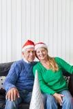Los pares mayores llevan el presente rojo del sombrero de la Navidad de santa Imágenes de archivo libres de regalías