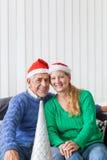 Los pares mayores llevan el presente rojo del sombrero de la Navidad de santa Fotos de archivo