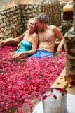 Los pares mayores que se relajaban en pétalo de la flor cubrieron la piscina en el balneario Imagen de archivo