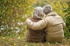 Los pares mayores que se sientan con el suyo apoyan el abarcamiento en parque del otoño Imagen de archivo