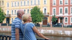 Los pares mayores se colocan en el muelle de la mirada del canal alrededor Viaje de los pensionistas en St Petersburg, Rusia almacen de metraje de vídeo