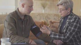 Los pares mayores se sientan en el sofá y la medición de la mujer sirve la presión arterial con el dispositivo del tonometer almacen de metraje de vídeo