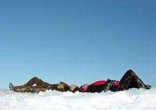 Los pares mienten en nieve y el reloj para arriba Foto de archivo libre de regalías