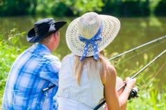 Los pares, mujer y hombre, con las cañas de pescar se divierten pescar con caña fotos de archivo libres de regalías