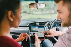 Los pares multiétnicos del amante utilizan el sistema de navegación en smartphone en coche Uso del teléfono móvil o concepto mode foto de archivo libre de regalías