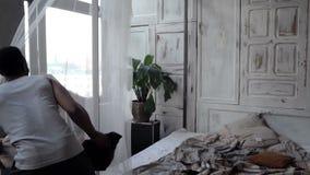 Los pares multiétnicos en pijamas tienen lucha al lado de la almohada La mujer corre lejos de hombre, se divierte en la cama Cáma metrajes