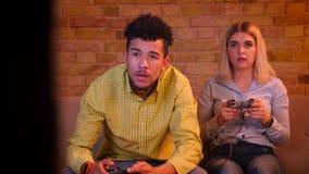 Los pares multinacionales juegan el videojuego con la palanca de mando que es absorbida y atenta en hogar acogedor almacen de video