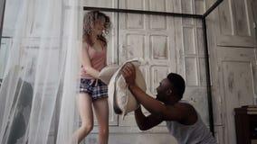 Los pares multirraciales se divierten en la mañana El hombre y la mujer en pijamas tienen lucha con las almohadas Cámara lenta almacen de video