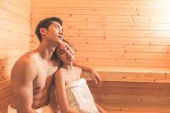 Los pares o los amantes asiáticos jovenes tienen relajación romántica en el ro de la sauna Foto de archivo