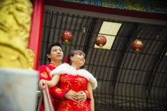 Los pares preciosos con el traje del qipao abrazan en templo chino Foto de archivo