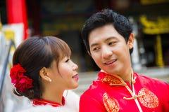 Los pares preciosos con el traje del qipao están en templo chino Imagenes de archivo