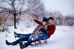 Los pares preciosos disfrutan de un paseo del trineo El sledding precioso de los pares Fotografía de archivo libre de regalías