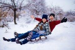Los pares preciosos disfrutan de un paseo del trineo El sledding precioso de los pares Imagen de archivo