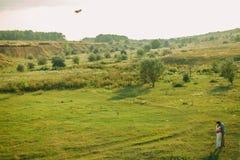 Los pares preciosos juegan con el juguete de la cometa del aire en el prado verde Imágenes de archivo libres de regalías