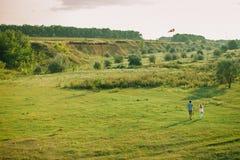 Los pares preciosos juegan con la cometa del aire del cielo en el prado verde Fotografía de archivo libre de regalías
