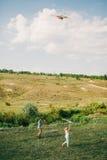 Los pares preciosos juegan con la cometa del aire en el prado verde Foto de archivo