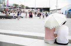 Los pares preciosos que se sientan en el banco y que comparten una sensación romántica de la demostración del paraguas en el puer foto de archivo libre de regalías