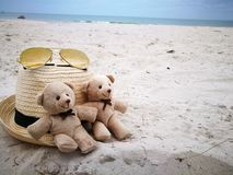Los pares preciosos refieren la playa blanca de la arena con el sombrero y los vidrios de sol en Hua Hin varan, artículo y los ac fotos de archivo