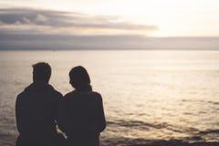 Los pares que abrazan en la playa en salida del sol del océano del fondo, siluetean a dos personas románticas que abrazan y que m foto de archivo