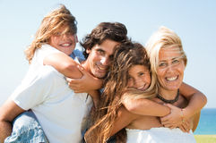 Los pares que dan a niños llevan a cuestas la sonrisa de los paseos fotos de archivo libres de regalías