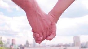 Los pares que llevan a cabo las manos en el fondo de la ciudad almacen de video