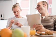 Los pares que se ríen de una tabla miran tecnología fotografía de archivo