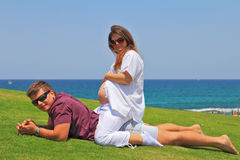 Los pares que se relajan en la hierba por el mar Fotografía de archivo libre de regalías