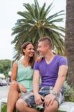 Los pares que se sientan cerca de la palmera y que pasan gran tiempo Foto de archivo