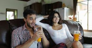 Los pares que se sientan en el coche In Living Room beben el zumo de naranja, el hombre joven y a la mujer por mañana hablando el metrajes