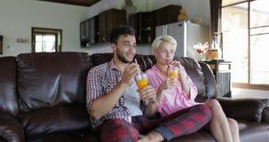 Los pares que se sientan en el coche In Living Room beben el zumo de naranja, el hombre joven y a la mujer por mañana hablando el almacen de video