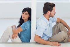 Los pares que se sientan son separados por la pared Foto de archivo