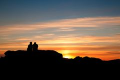 Los pares que tienen se relajan, en la puesta del sol en Tofino, isla de Vancouver, Canadá Imagen de archivo