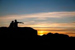 Los pares que tienen se relajan, en la puesta del sol en Tofino, isla de Vancouver, Canadá Imágenes de archivo libres de regalías