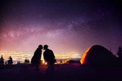 Los pares románticos acercan a la hoguera en el cielo estrellado foto de archivo